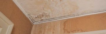 What Causes Damp? Signs of dampness in the corner of a ceiling.