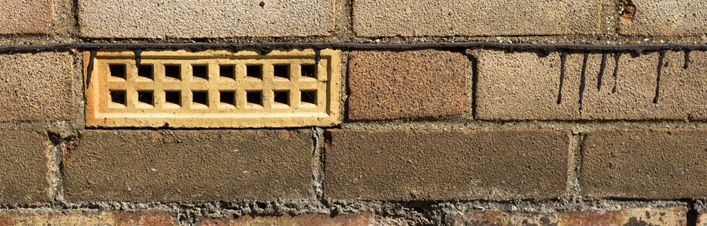 Air brick and damp proofing on the exterior of a house.